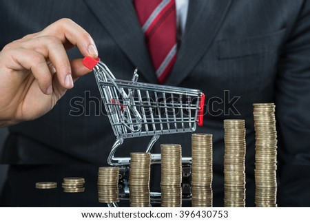 Close-up Of Businessman With Stack Of Coins And Small Shopping Cart At Desk
