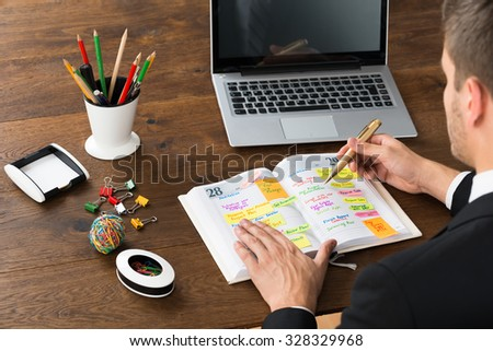 Close-up Of Businessman Writing Office Schedule In Diary With Stationery And Laptop At Desk - stock photo