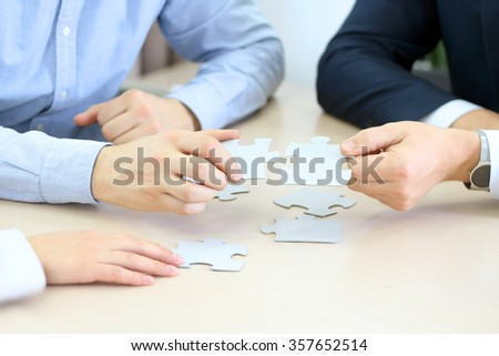 Close-up Of Businessmen Hand Connecting Jigsaw Puzzle - stock photo
