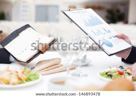 Close-up of businessmen planning work while having business lunch - stock photo