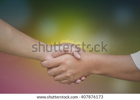 Close up of businessmen shaking hands on abstract bokeh background