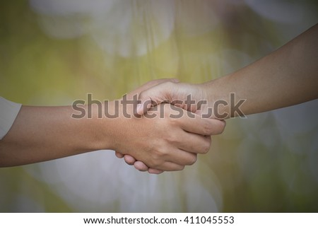 Close up of businessmen shaking hands on nature background