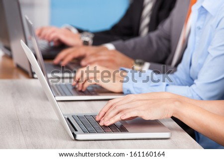 Close-up Of Businesspeople In A Row At Desk Using Laptop - stock photo