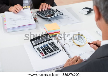 Close-up Of Businesspeople Scrutinizing Bills With Magnifying Glass - stock photo