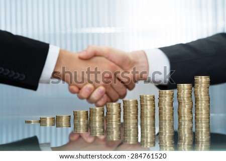 Close-up Of Businesspeople Shaking Hand In Front Of Stacked Coins - stock photo