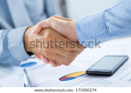 Close Up Of Businesspeople Shaking Hands At Desk - stock photo