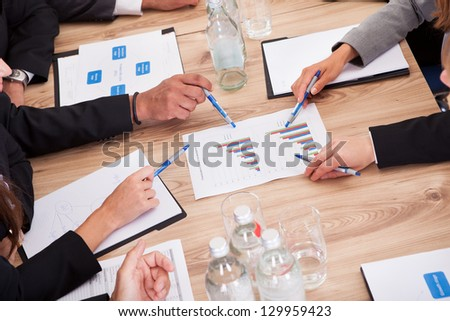 Close-up of Businesspeople Sitting At Conference Table Communicating