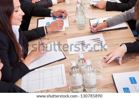 Close-up of Businesspeople Sitting At Conference Table Communicating - stock photo