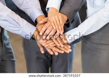 Close-up of businesspeople stacking hands in meeting at office