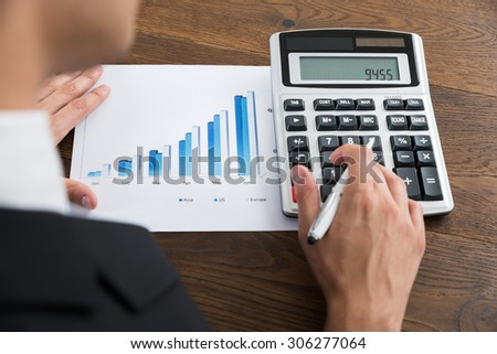Close-up Of Businessperson Analyzing Graph And Using Calculator At Desk - stock photo