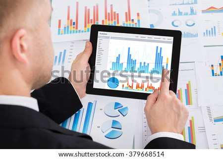 Close-up Of Businessperson Analyzing Graph On Digital Tablet In Office - stock photo