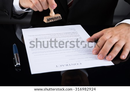 Close-up Of Businessperson Approving Contract Paper With Stamper - stock photo