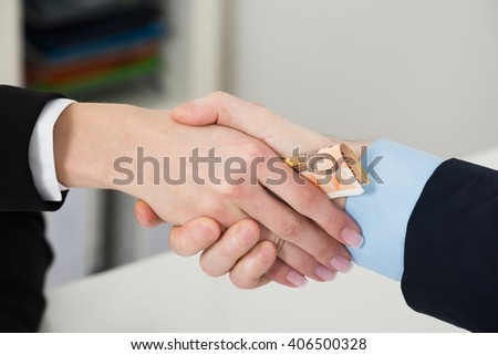 Close-up Of Businessperson Bribing Partner While Shaking Hand In Office