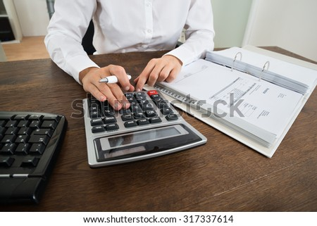 Close-up Of Businessperson Calculating Financial Expenses With Calculator At Desk - stock photo