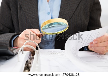 Close-up Of Businessperson Checking Bills With Magnifying Glass - stock photo