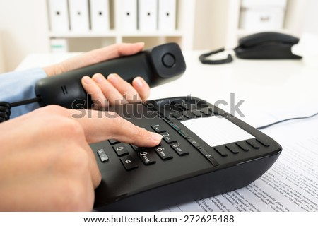 Close-up Of Businessperson Dialing Number On Telephone Keypad - stock photo