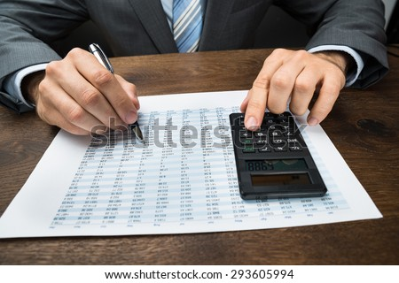 Close-up Of Businessperson Doing Calculation With Calculator In Office - stock photo