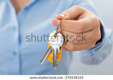 Close-up Of Businessperson Hand Holding Key In Hand - stock photo