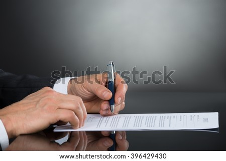 Close-up Of Businessperson Hand Signing Contract Paper With Pen At Desk - stock photo