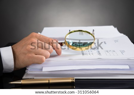 Close-up Of Businessperson Hands Analyzing Receipt With Magnifying Glass At Desk - stock photo