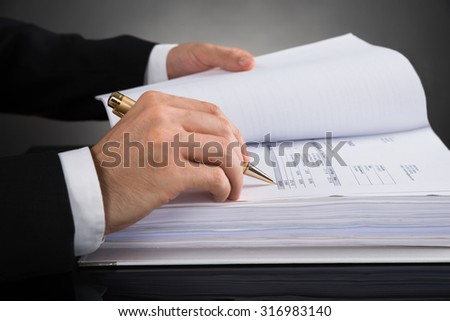 Close-up Of Businessperson Hands Calculating Invoice At Desk - stock photo