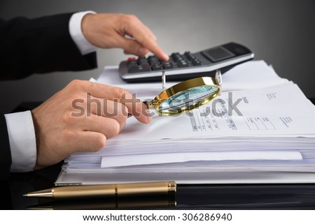 Close-up Of Businessperson Hands Checking Invoice With Magnifying Glass At Desk - stock photo