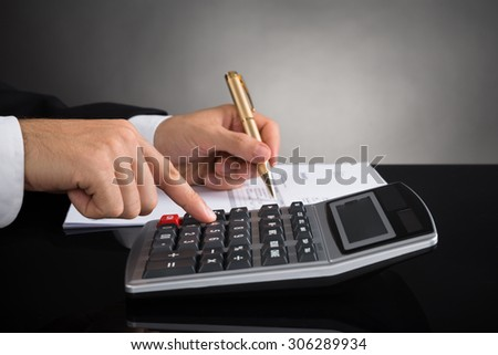 Close-up Of Businessperson Hands Doing Calculation At Desk - stock photo