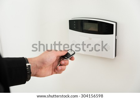 Close-up Of Businessperson Hands Operating Entrance Security System With Remote Control - stock photo