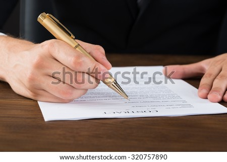 Close-up Of Businessperson Hands With Pen Over Contract Paper At Desk - stock photo