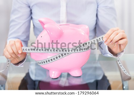 Close-up Of Businessperson Holding Measuring Tape Around An Pink Piggybank - stock photo