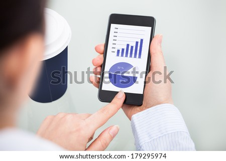 Close-up Of Businessperson Holding Mobile Phone Showing Graph - stock photo