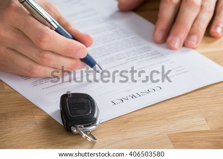Close Up Of Businessperson Holding Pen On A Contract Paper With Car Key On It - stock photo