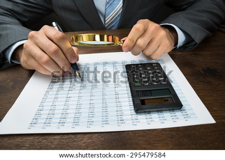 Close-up Of Businessperson Inspecting Financial Data With Magnifying Glass - stock photo