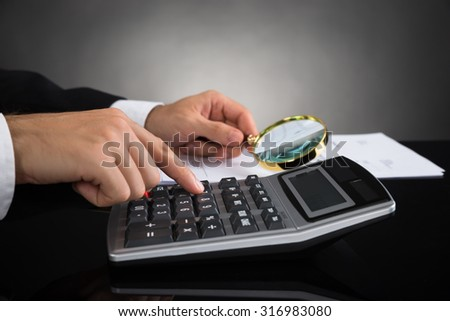 Close-up Of Businessperson Inspecting Invoice With Magnifying Glass And Calculator - stock photo