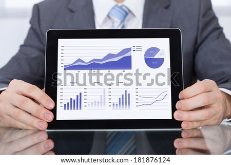 Close-up Of Businessperson Showing Graph On Digital Tablet - stock photo