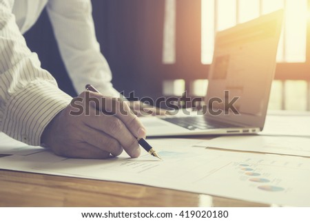 Close-up Of Businessperson Signing Contract,Man writing paper at the desk, man writing with pen and reading books at table,man Signing, Contract, Form. in office ,morning light ,selective focus.