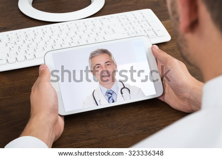 Close-up Of Businessperson Videochatting With Senior Doctor On Mobile Phone - stock photo