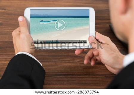 Close-up Of Businessperson Watching Video On Mobile Phone In Office - stock photo
