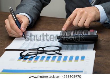 Close-up Of Businessperson With Graph Calculating Tax In Office - stock photo
