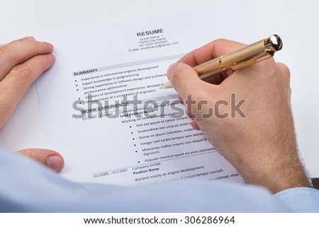 Close-up Of Businessperson With Resume And Pen - stock photo