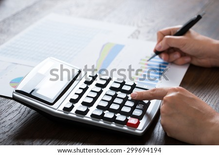 Close-up Of Businesswoman Analyzing Financial Report With Calculator At Wooden Desk - stock photo