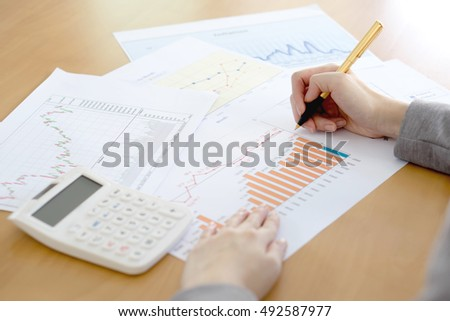 Close-up Of Businesswoman Analyzing Graph With Calculator At Desk