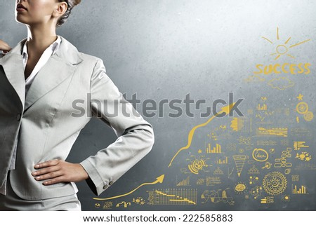 Close up of businesswoman and business sketches on cement wall