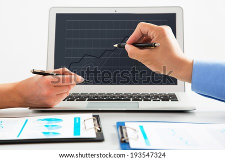 Close-up of businesswoman explaining a financial plan to colleague - stock photo