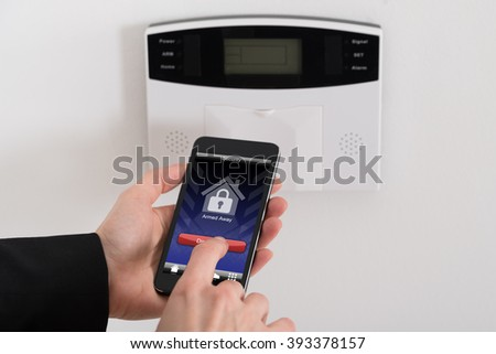 Close-up Of Businesswoman Hand Disarming Security System Of Door
