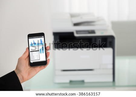 Close-up Of Businesswoman Hand Giving Print Command On Smart Phone