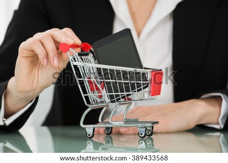 Close-up Of Businesswoman Hand Holding Cart With Mobile Phone