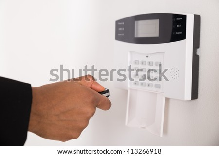 Close-up Of Businesswoman Hand Using Remote Control For Operating Door Security System