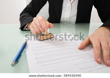 Close-up Of Businesswoman Hand Using Stamper On Document - stock photo