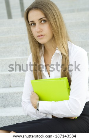 Close-up of businesswoman holding a folder outside - stock photo